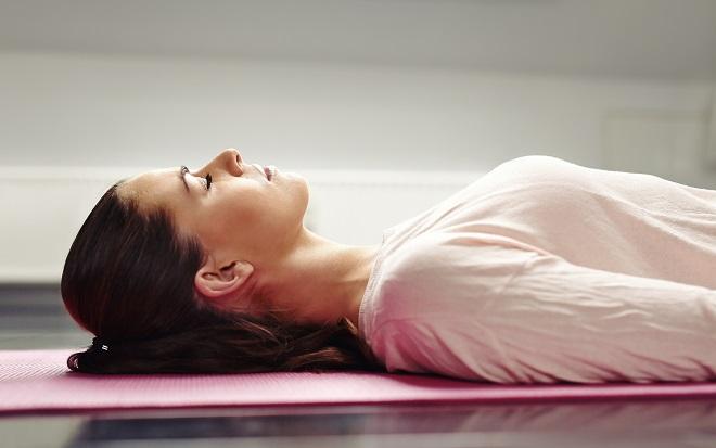 kvinde mediterer på yogamåtte