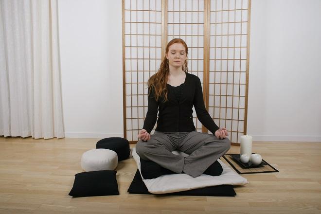Kvinde sidder behageligt på meditationsunderlag og meditationspude