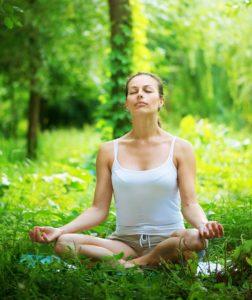 Afslappet kvinde mediterer i naturen
